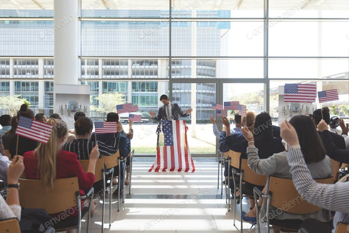 Politician speaking at a business seminar in office building with american flags