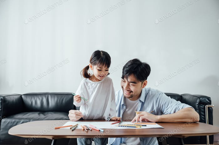 Vater und Tochter zeichnen zusammen zu Hause