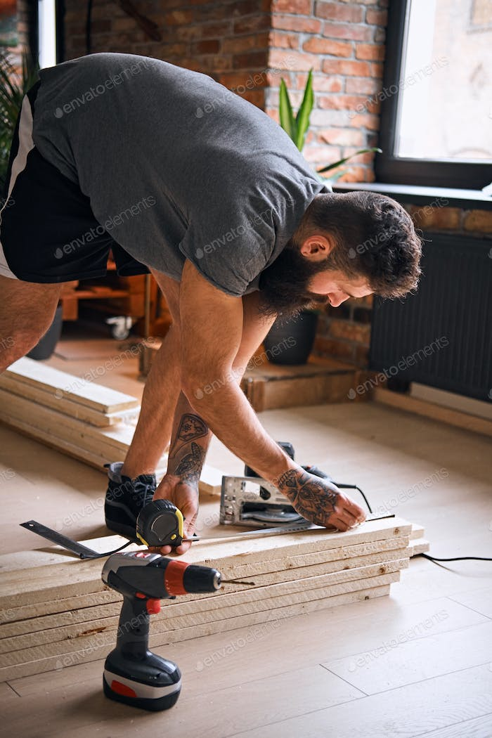 Carpenter measuring boards in a room with loft interior.