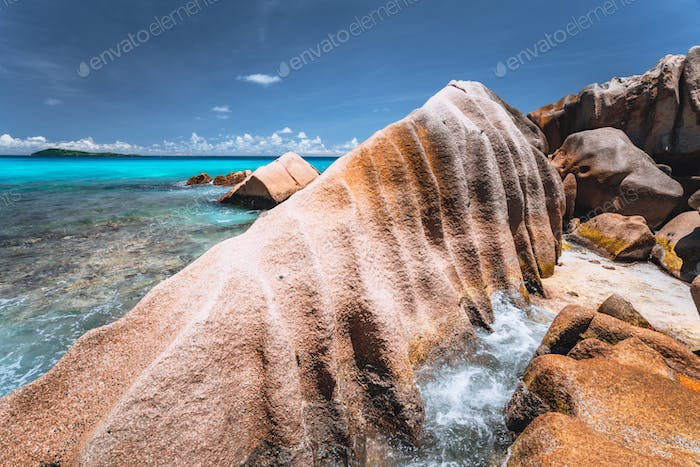 Bizarre formed rocks on Anse Cocos beach, La Digue island, Seychelles. Blue ocean bay in background