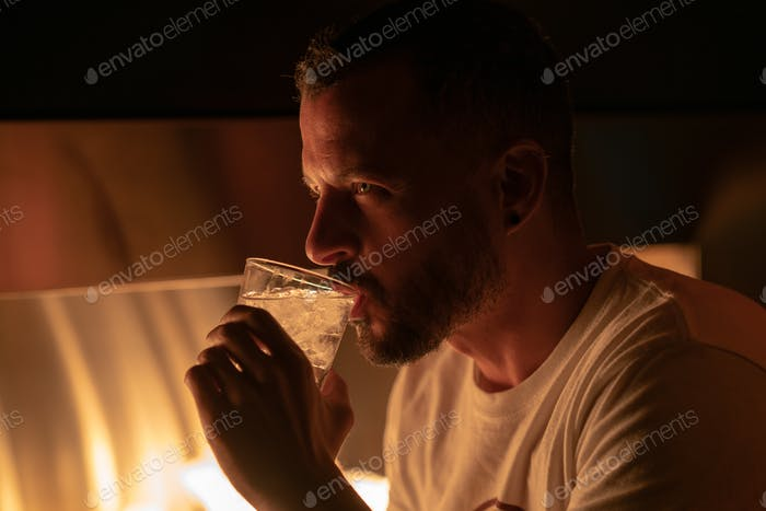 Handsome man drinking a glass of vodka near a fire pit