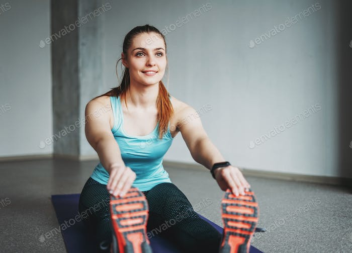 Attractive fit young woman sport wear fitness girl model doing stretching