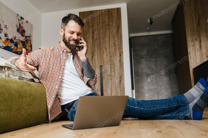 Smiling brunette bearded man talking on mobile phone