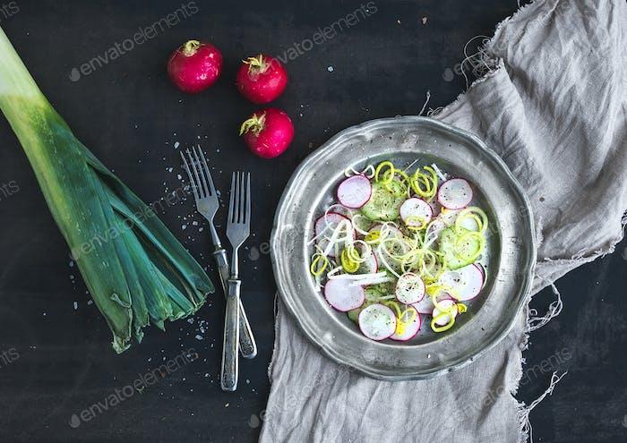 Spring salad with leek, radish and cucumber in vintage metal plate