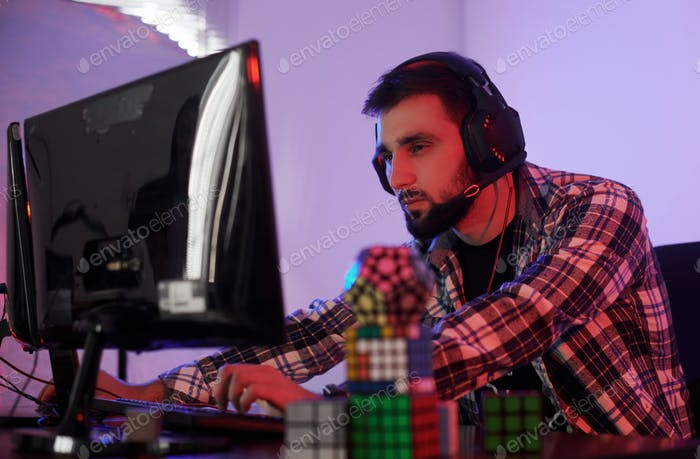 Portrait of young bearded pro gamer playing in online video game