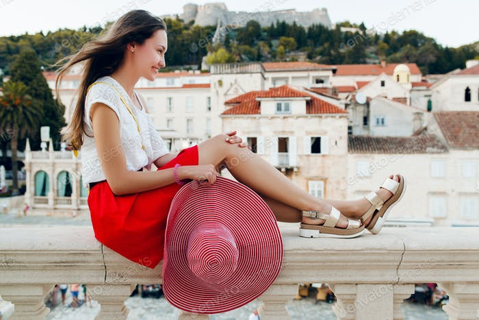 pretty woman with red hat on vacation legs in sandals