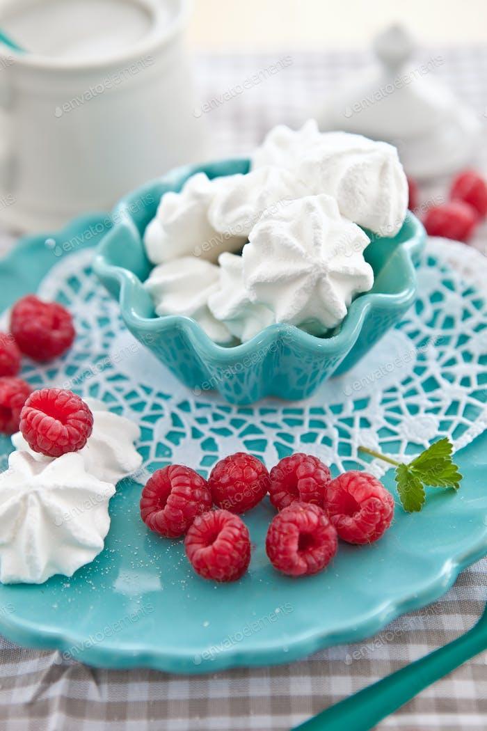 Meringues and raspberries on a blue plate