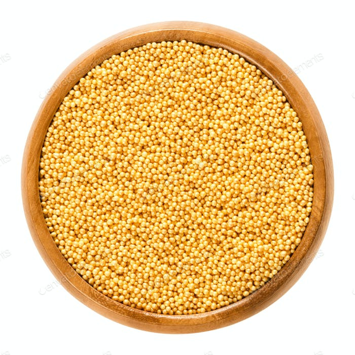 Gold nonpareils in wooden bowl on white background
