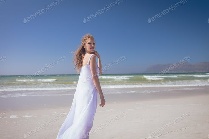 Beautiful woman smiling and standing at beach on a sunny day