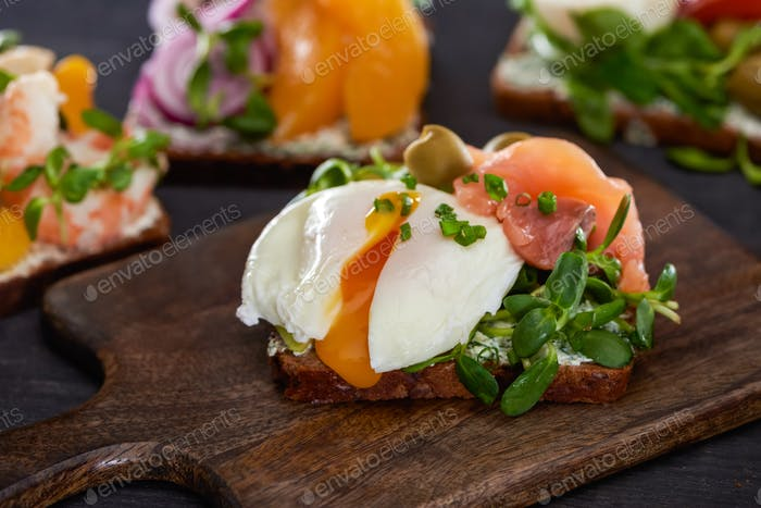 selective focus of danish smorrebrod sandwich with poached egg near salmon on wooden cutting board
