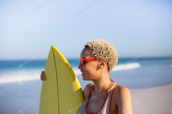 Seitenansicht der schönen Afroamerikanerin stehend mit Surfbrett am Strand in der Sonne