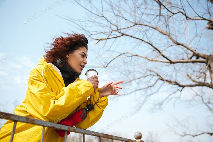 Happy african curly young woman wearing yellow coat drinking coffee.