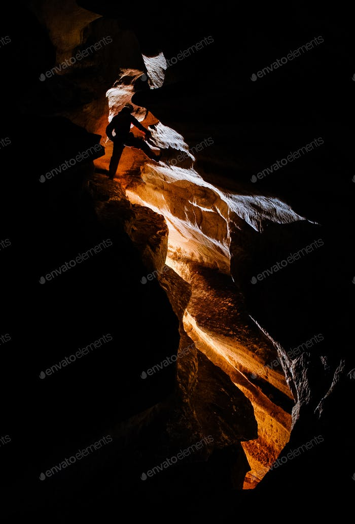 Spelunker exploring and climbing in a deep cave