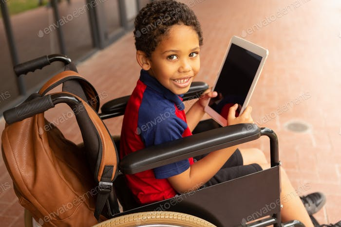 Disabled schoolboy with digital tablet looking at camera in corridor at elementary school