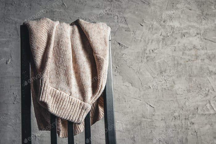 Knitted beige sweater on the back of a white wooden chair