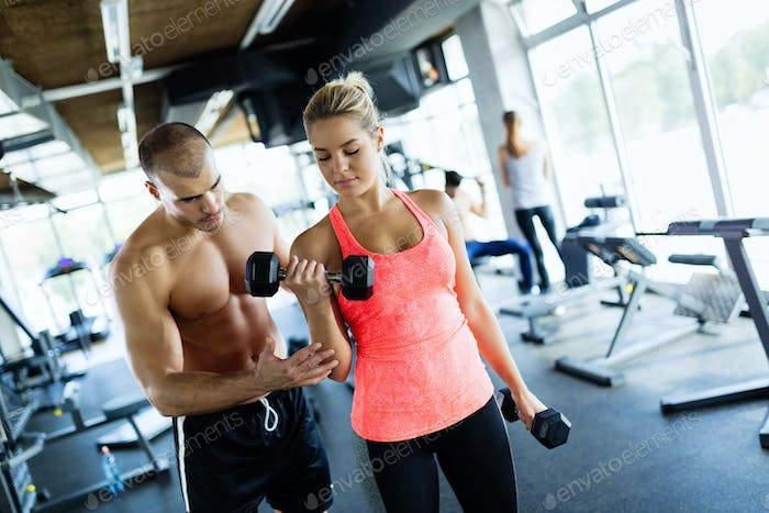 Young adult woman doing exercises in gym with trainer