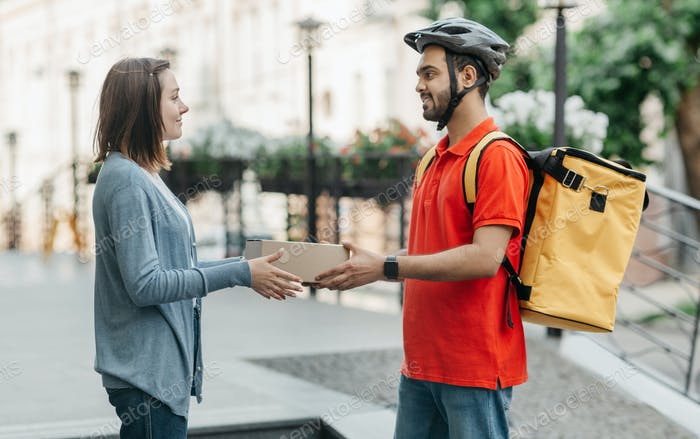 Woman takes online purchase from courier. Deliveryman in helmet, with backpack gives box to client