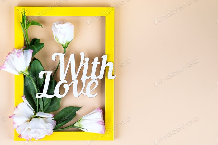 Empty yellow frame, With Love word and flowers eustoma on beige paper background with copy space