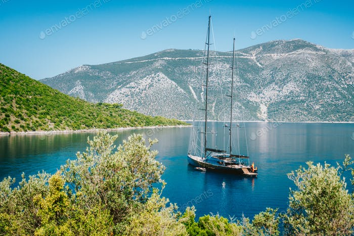Summer vacation in Greece. Luxury black private yacht at anchor in beautiful sea lagoon. Ithaka