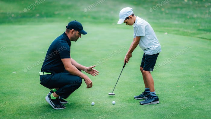 Golf Putting Training. Golf Instructor with Young Boy Practicing on the Putting Green