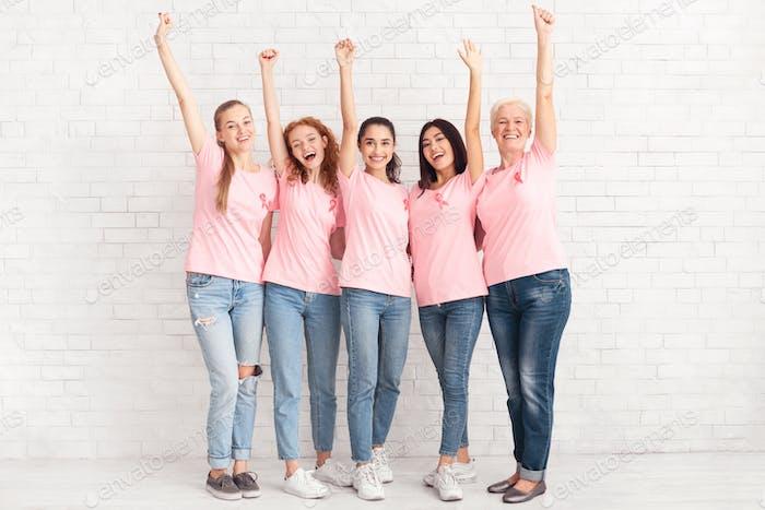 Frauen mit rosa Bändern heben Hände stehend über weiße Wand