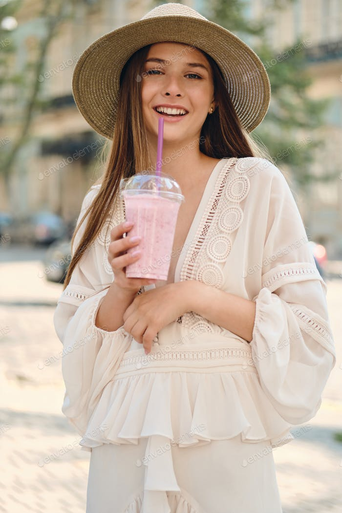 Young cheerful girl in white dress and hat holding smoothie happily looking in camera on city street