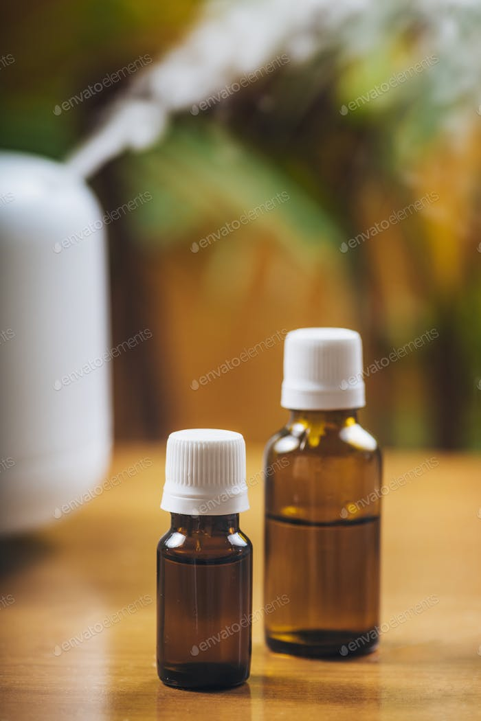 Natural Essential Oil Bottles and Aroma Therapy Diffuser on a Wooden Table