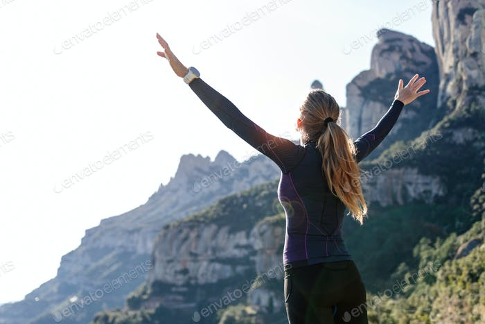 Trail runner with open arms raised while enjoying nature on moun