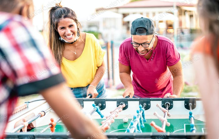 Multiracial friends play kicker table football at open space bar