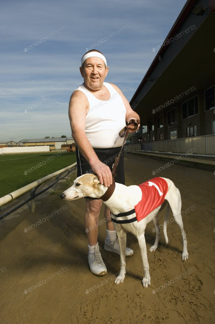 Man in sportswear standing on a racetrack, holding a white greyhound wearing red bib with number one