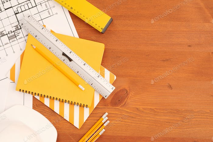 Flatlay of copybooks, rulers and pencils by unfolded blueprints with sketches