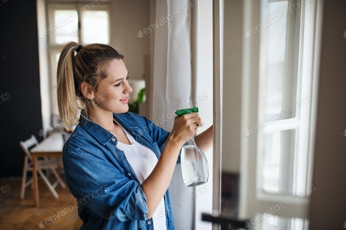 Young woman standing indoors at home, cleaning windows.