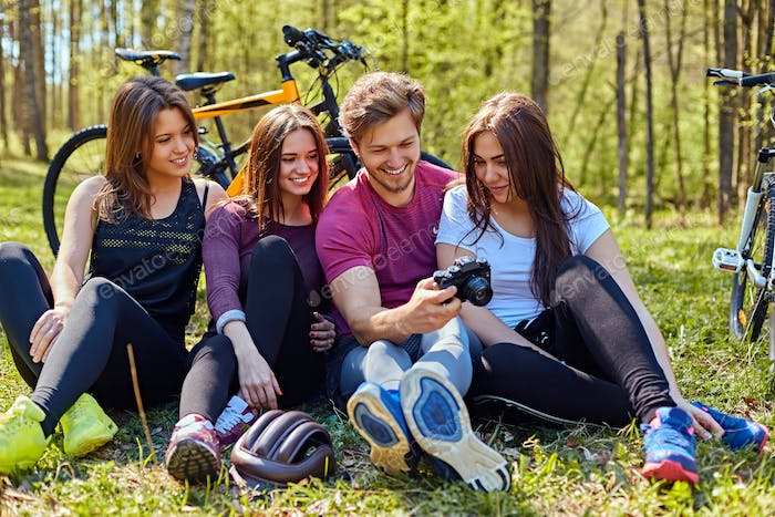 Groupe of people relaxing after bicycle ride in a forest.