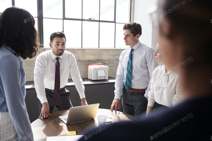 Young male manager addressing colleagues in meeting room