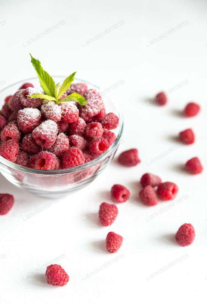 Fresh raspberries in the glass bowl