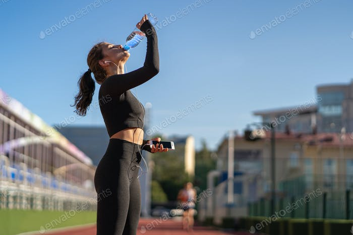 Thirsty girl drinking water from plastic bottle resting after jogging on stadium on sunny day