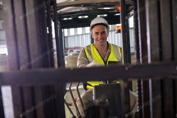 Portrait of worker driving forklift