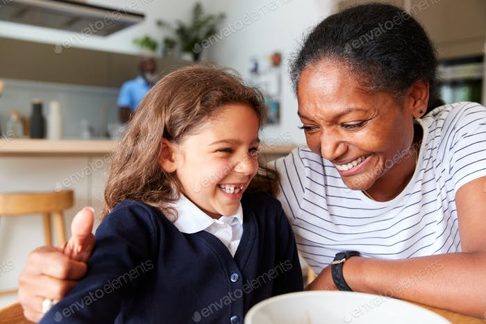 Grandparents Sitting In Kitchen With Granddaughter Eating Breakfast Before Going To School