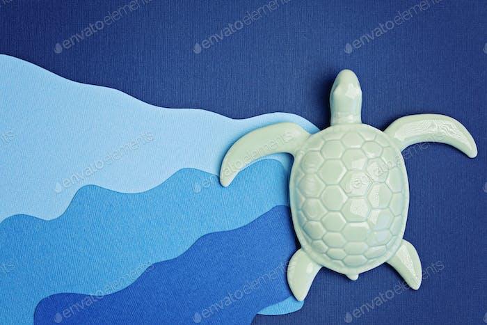 Tortuga y papel cortados para el día mundial de los océanos. Guarda el papel de los océanos sobre fondo azul. Medio ambiente