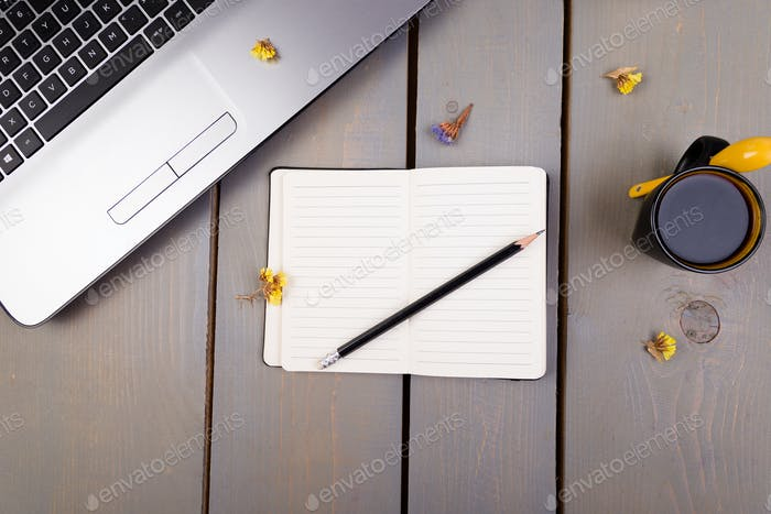 Notebook, coffee and flowers for female home or office workplace on wooden background. top view