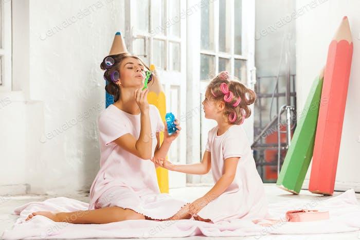 Kleines Mädchen sitzen mit ihrer Mutter und spielen
