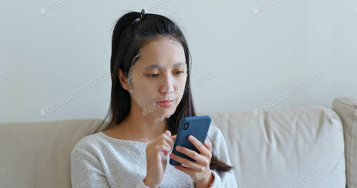 Woman apply paper mask on face at home with use of mobile phone
