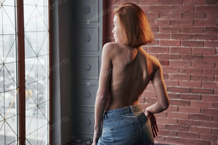 With style. Hot young blonde with bare chest and jeans stands against the window and brick wall