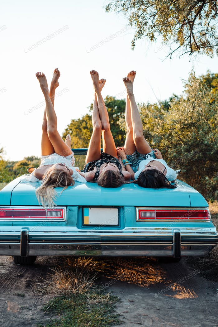 Three girls are lying on the trunk