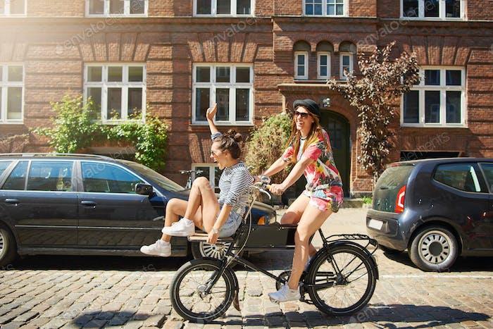Unbeschwerte Freundinnen, die zusammen mit dem Fahrrad durch die Stadt fahren