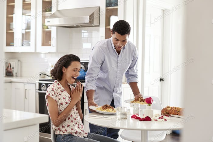 woman sitting at the table in the kitchen, her partner surprising her by serving a romantic meal