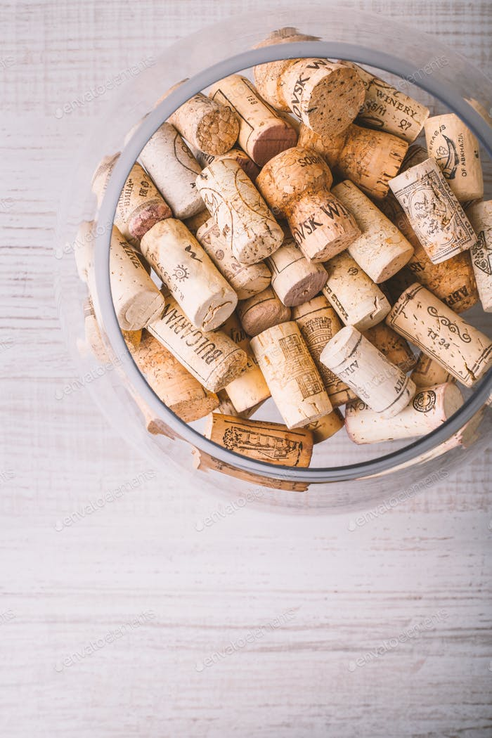 Glass vase with corks on the wooden table
