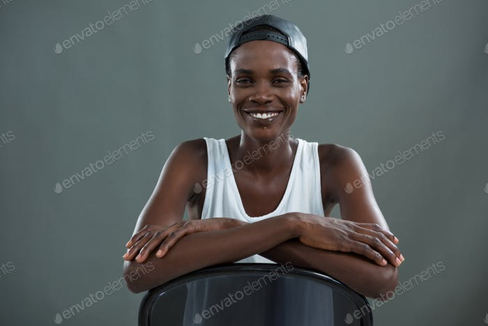 Androgynous man in cap smiling at camera