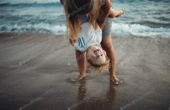 Young mother with a toddler boy standing on beach on summer holiday, having fun.