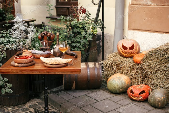 Pumpkins with scary faces on hay at cafe table. Happy halloween. Autumn market in town.